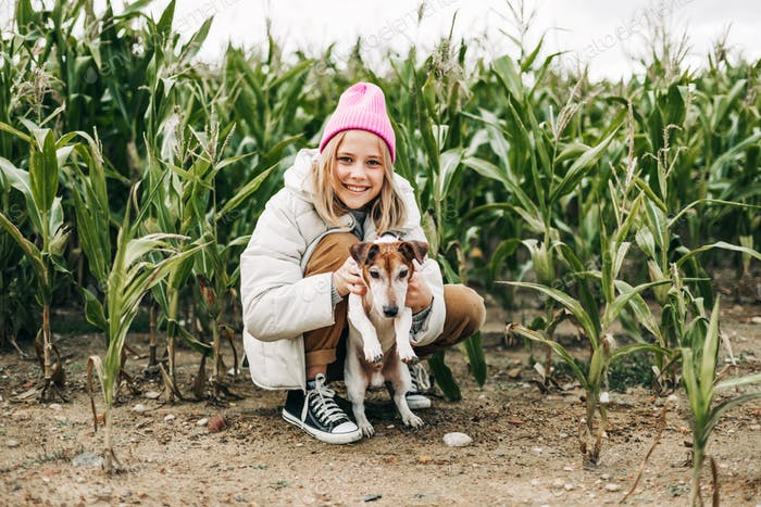 Happy teenage girl hugging her dog Jack Russell terrier in a field against