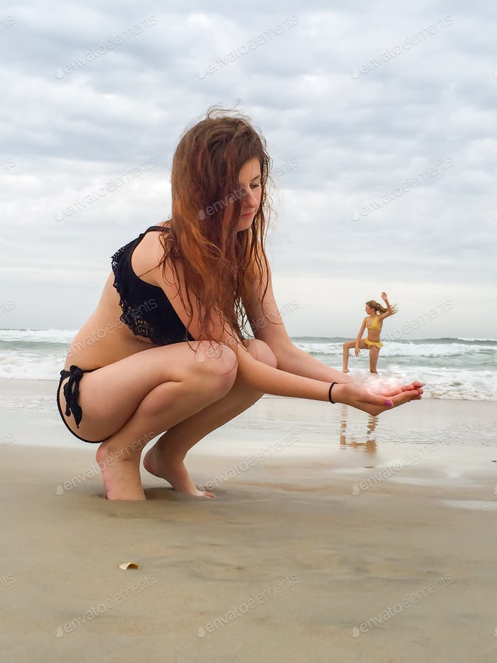 Two young women on beach with one supporting the other doing yoga poses in water along shoreline