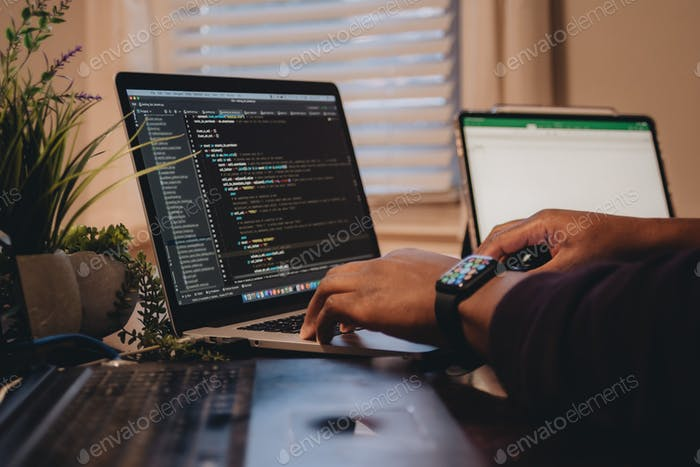 Hombre afroamericano sentado frente a la codificación de computadora, programación, desarrollador web