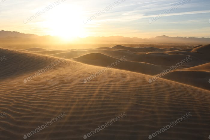 Wind and Dust Storm at Sunrise Over Desert Sand Dunes