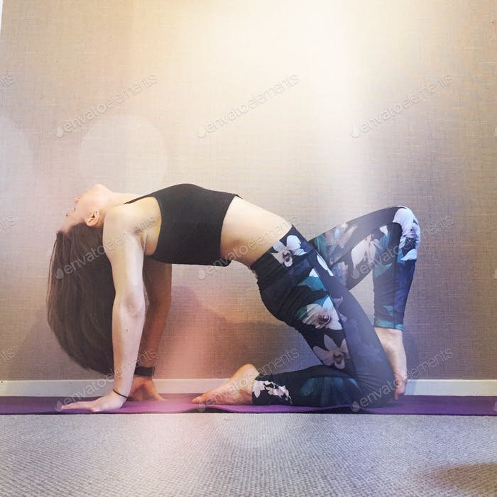 Millennial woman doing a yoga pose at home