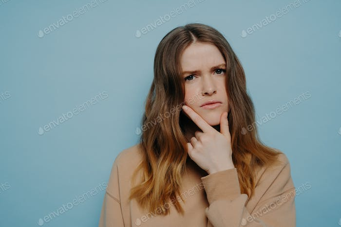Confused young woman looking at camera standing over blue background