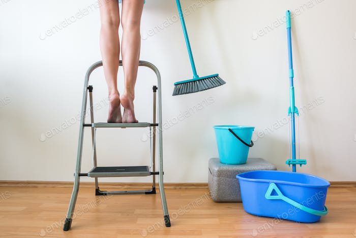 Young woman cleaning home with buckets and brush