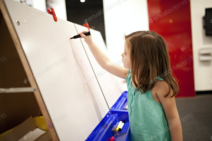 girl drawing on white board