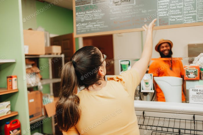 Young millennial woman shopping at a local small black owned business, convenience store, menu items