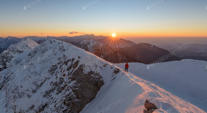 Male hiker at the sunrise in the mountains