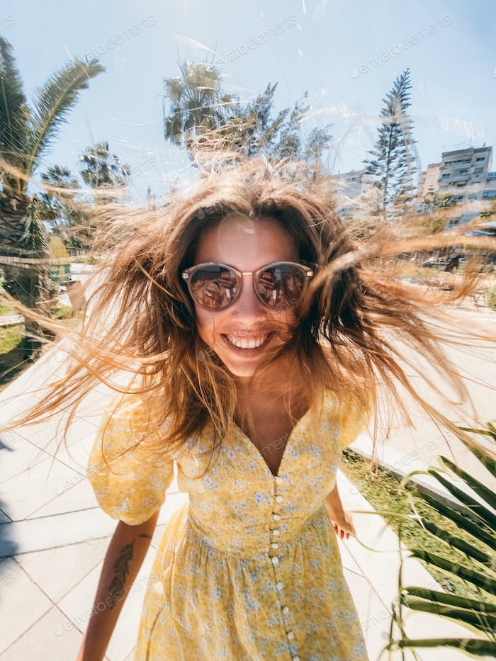 happy smiling woman with windy hairs in sunglasses