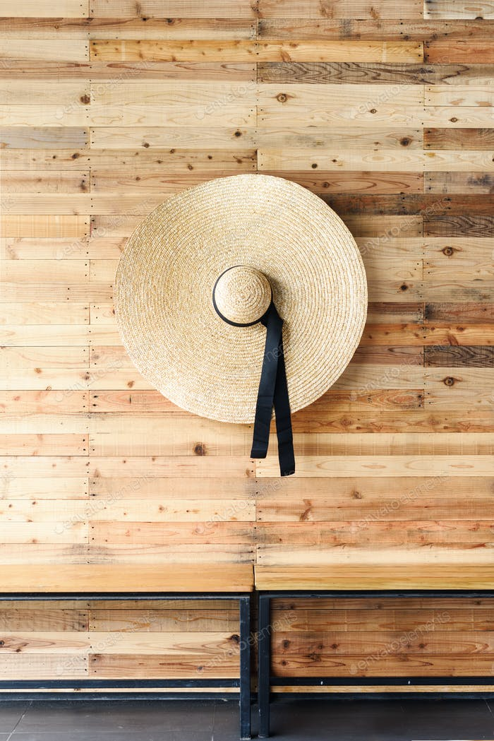 Bamboo rattan wicker hat hanging on the wall sheathed with lath. Asian handcraft. Vintage detail