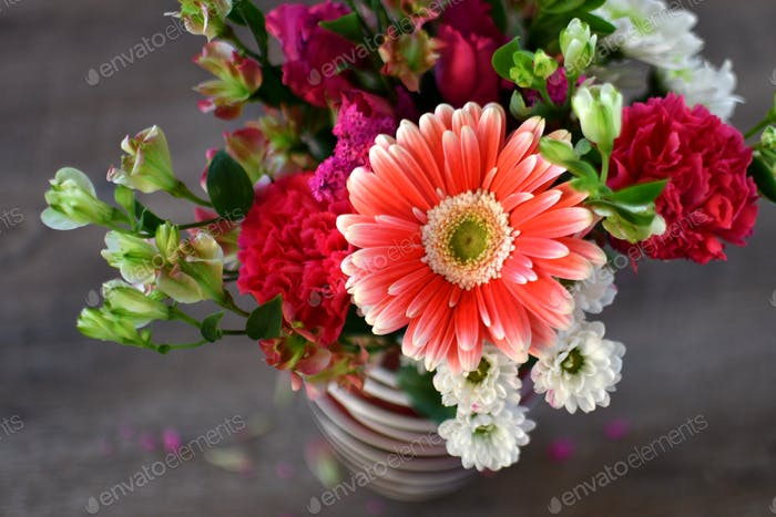 Bouquet of pink flowers featuring an orange Gerber daisy
