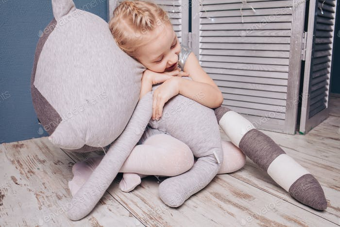little blonde girl hugging a big toy / childhood memories