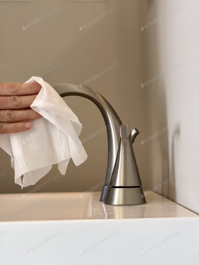 Cleaning the sink with a Clorox wipe