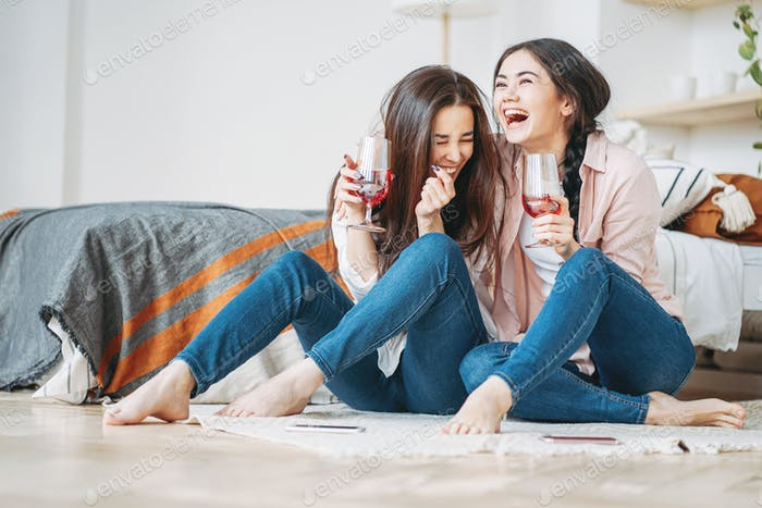 Young carefree laughing brunette girls friends in casual with glasses of wine having fun together on
