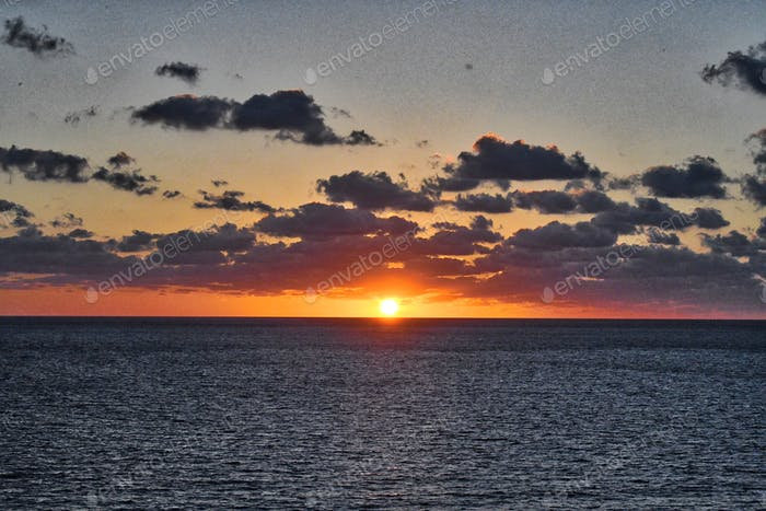 The sun was a brilliant orange as it appeared over the horizon in the early morning on the ocean