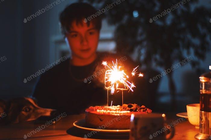 Junger Mann sitzt an einem Tisch und ein Hund beide Blick auf einen Geburtstagskuchen mit Feuer Wunderkerzen