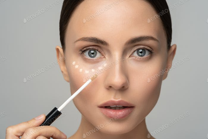 Woman with natural makeup applying corrector on flawless fresh skin, put concealer under eye area.
