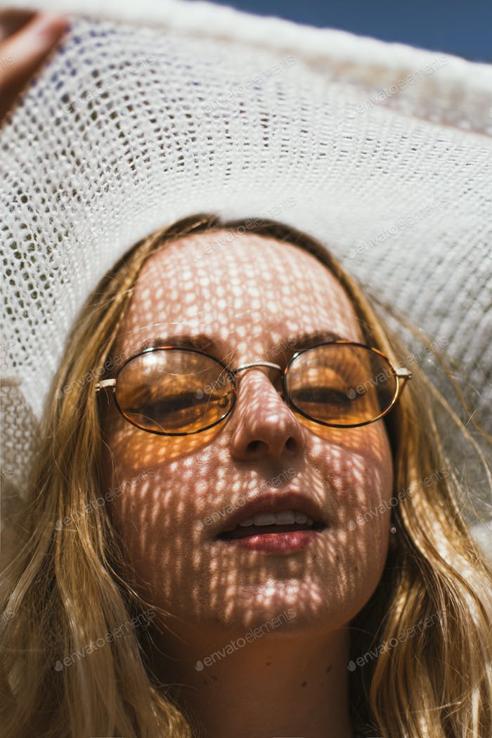 A cool young woman looks into camera as she shields her face from the sun with a jumper.