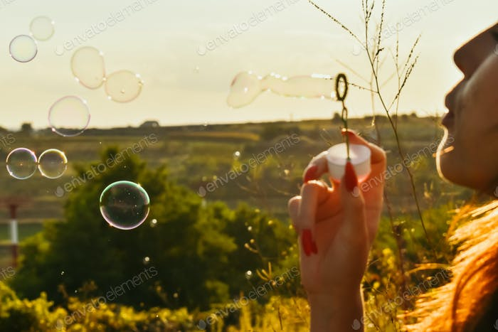 A girl making bubbles on open air