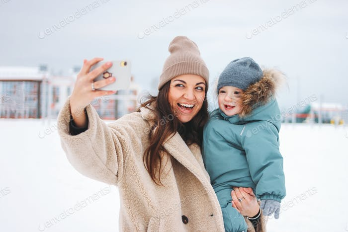 Young pretty mom brunette woman with cute baby boy in warm suit making selfie on the winter street