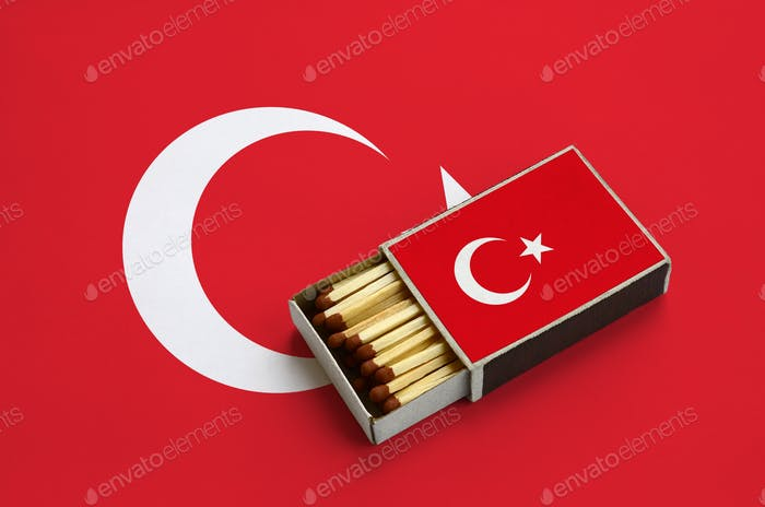 Turkey flag  is shown in an open matchbox, which is filled with matches and lies on a large flag.