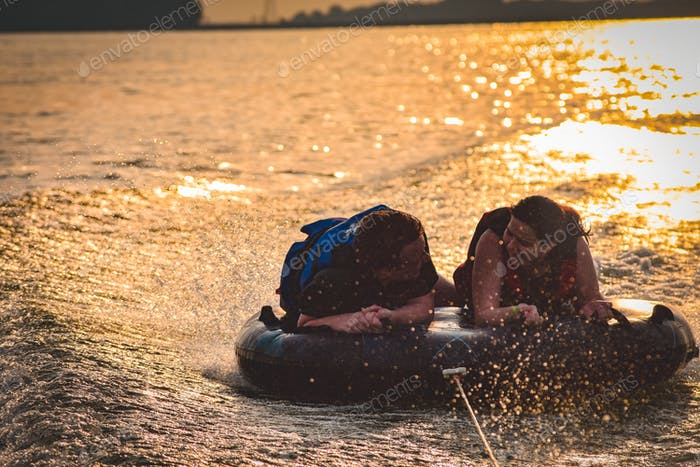 Brother and Sister enjoying the end to s summer day while riding a float by boat