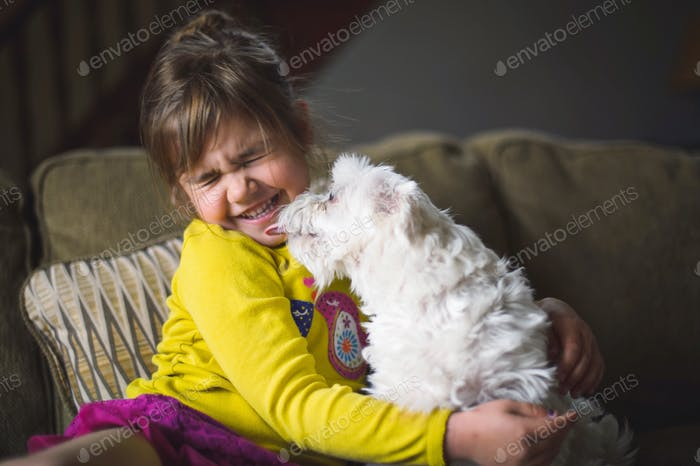 Kid with dog licking her face