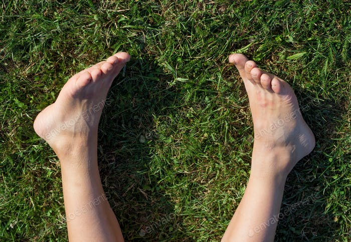 Bare foot at the green grass