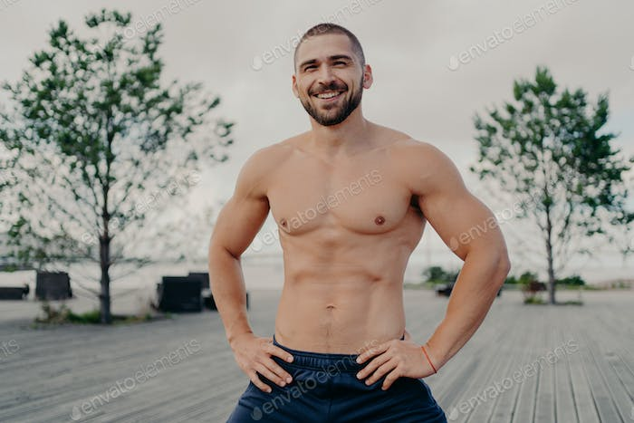 Handsome man with thick bristle keeps hands on waist, stands with naked muscular torso poses outdoor