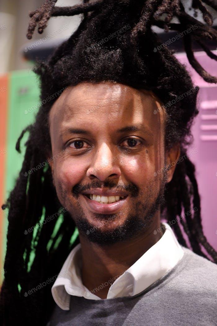 Retrato de un joven y sonriente hombre negro diverso con pelo salvaje con camisa y suéter con cuello