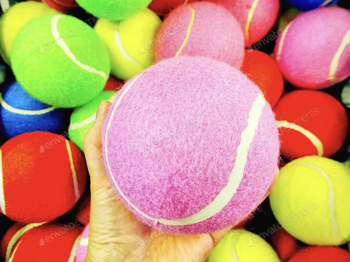 Bright and colorful pic of multi colored tennis balls with woman's hand holding a pink ball close up
