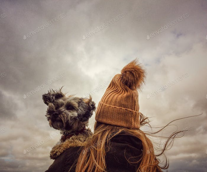 A rear view of fashionable young girl wearing a woolly bobble hat and holding her scruffy pet dog on
