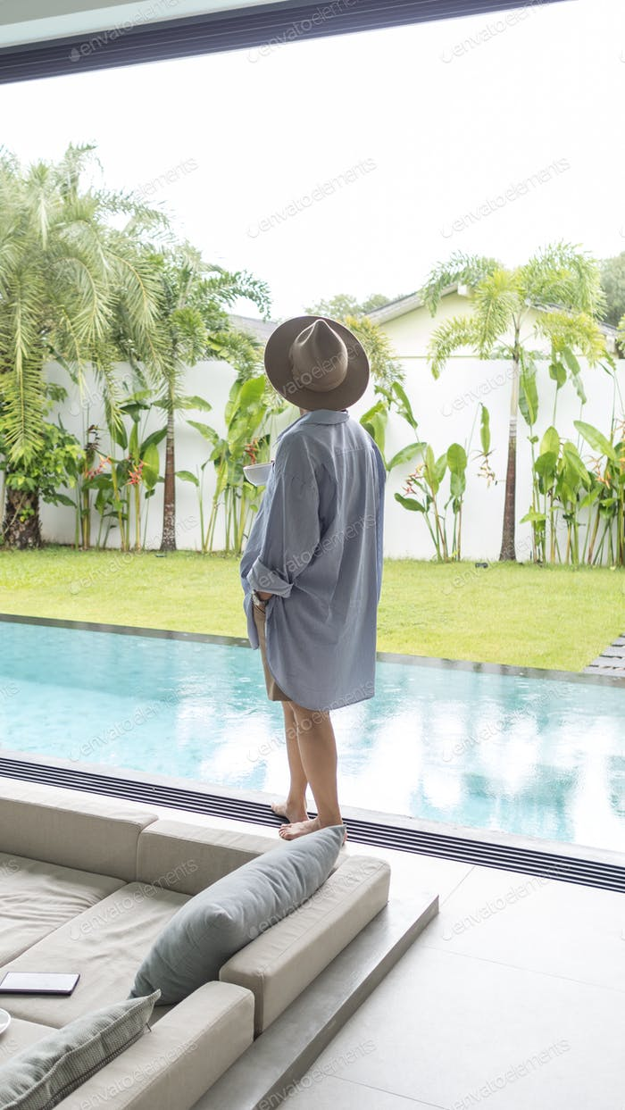 Young woman in hat standing and drinking coffee nearby swimming pool of villa. Tropical vacation.