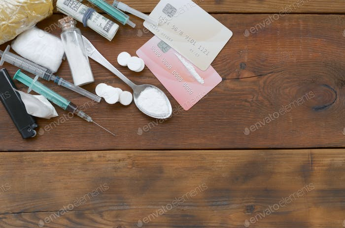 A lot of narcotic substances pills and devices for the preparation of drugs lie on an old wooden