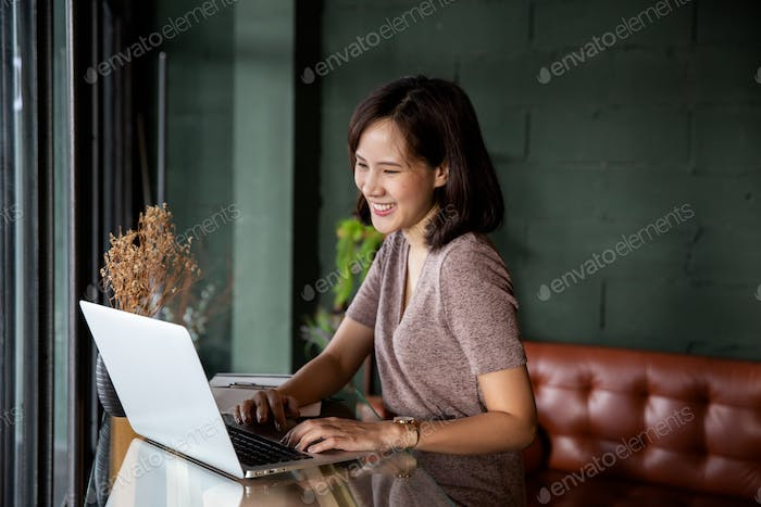 Young beautiful asian woman working at a coffee shop with a laptop.