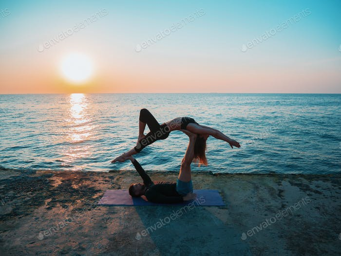 Acroyoga concept. Two sporty people practicing yoga in pair on nature sunrise background. Beautiful