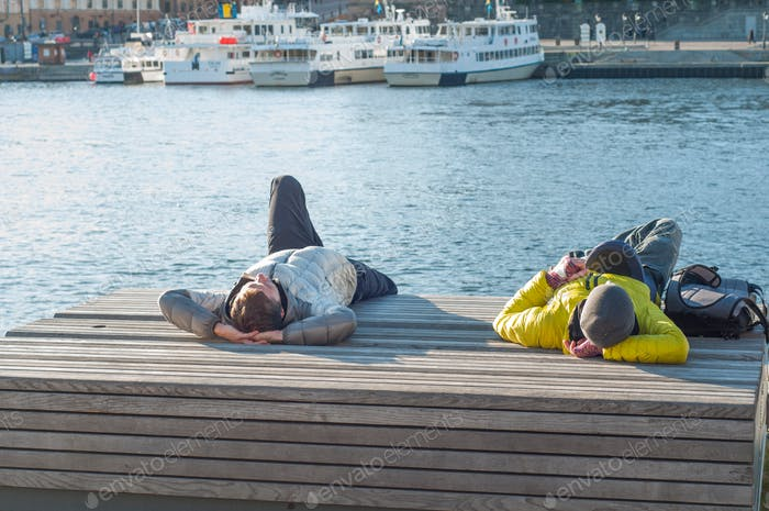 Two men relaxing on a wooden bench in a seaport of Stockholm. Beautiful autumn day in Stockholm.