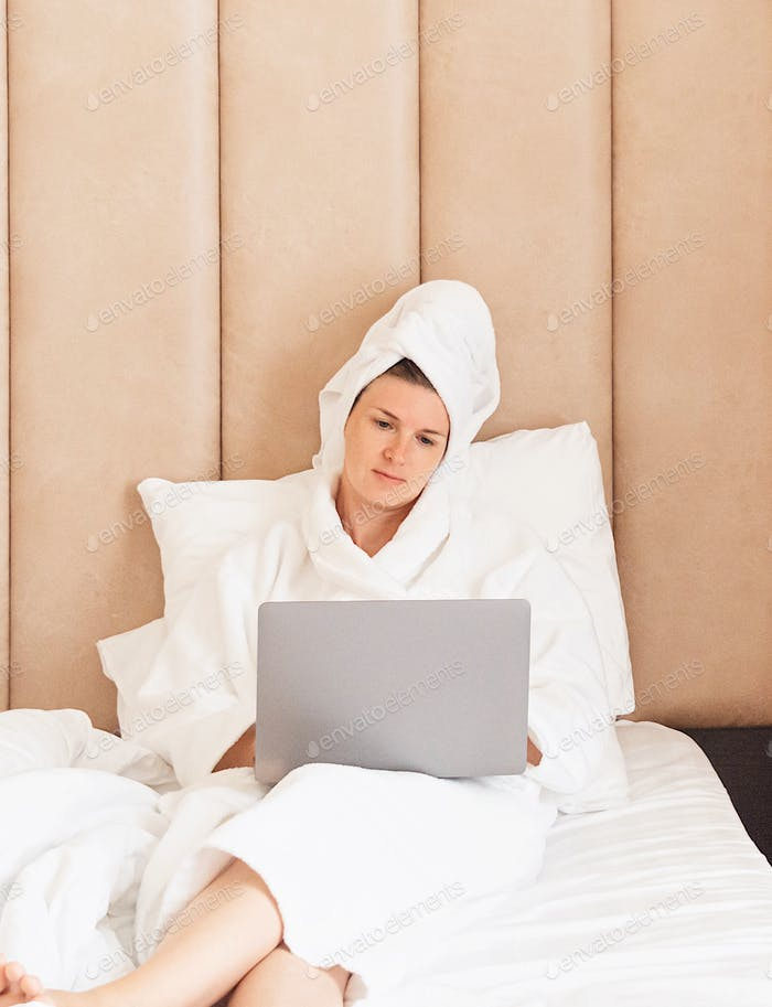 Young women with laptop in bed