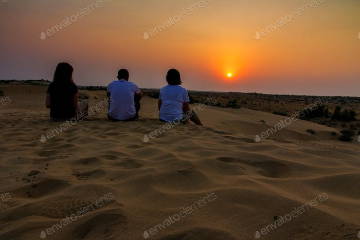 Three friends sitting on the sand looking the sunset at Thar desert in India