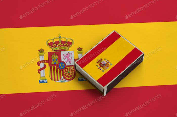 Spain flag  is pictured on a matchbox that lies on a large flag.