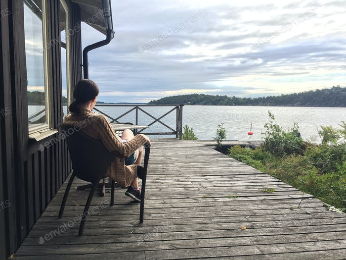 Young woman in a cardigan having morning coffee on a pier in Swedish countryside