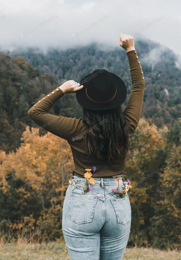 Вид сзади молодой женщины на природе, осень, осень, земляные тона, капризный, шляпа.