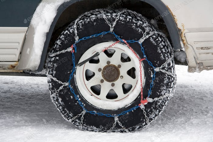Snow chains on the wheel of a 4X4 vehicle in Greenland.