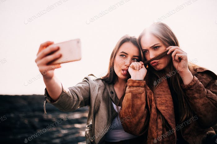 Young Girls taking selfie with smartphone pulling faces