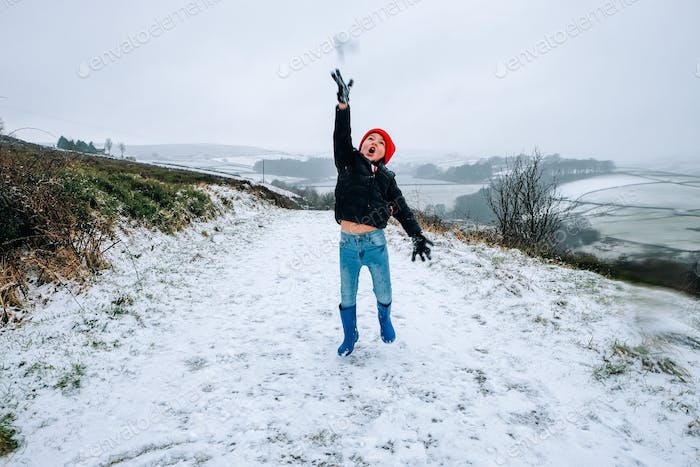 Young boy throwing snow in countryside Yorkshire, United Kingdom