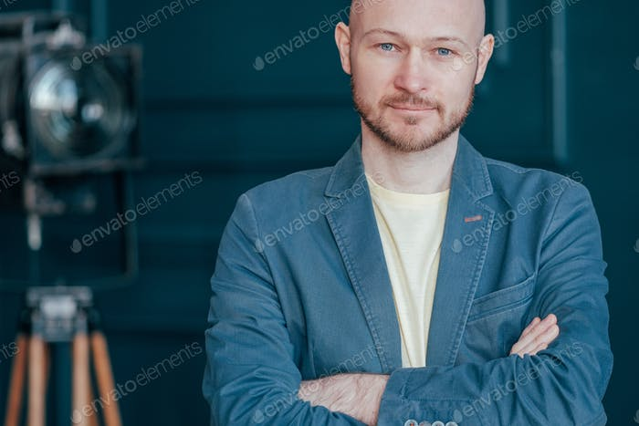 Portrait of attractive adult successful bald bearded man in suit on blue background, blogging