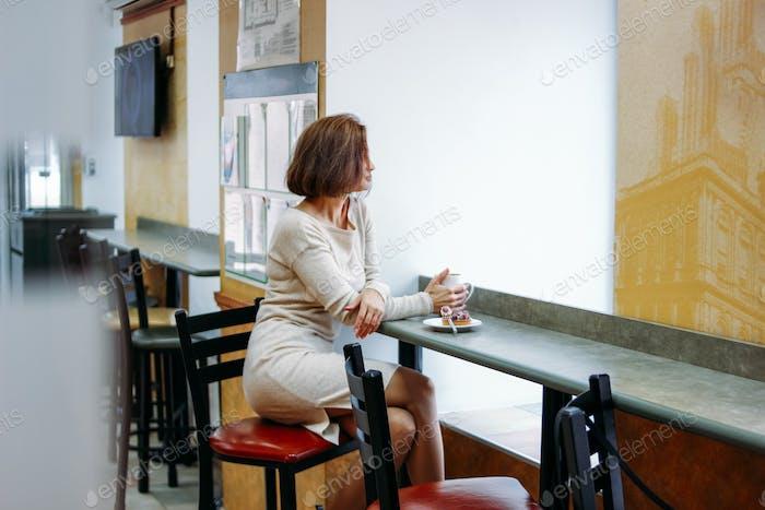 Charmante Brünette Frau sitzt am Fenster im Café mit Tasse Kaffee in den Händen