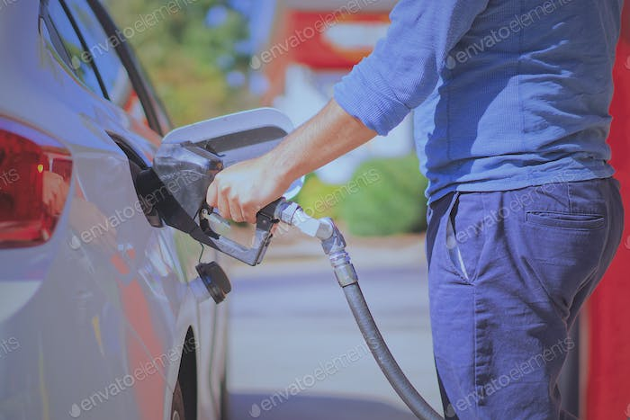 Man putting gasoline to his vehicle