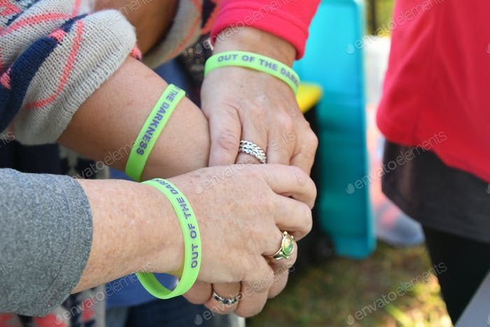 Woman wearing Suicide prevention Out of Darkness wristbands joining hands as they support each other