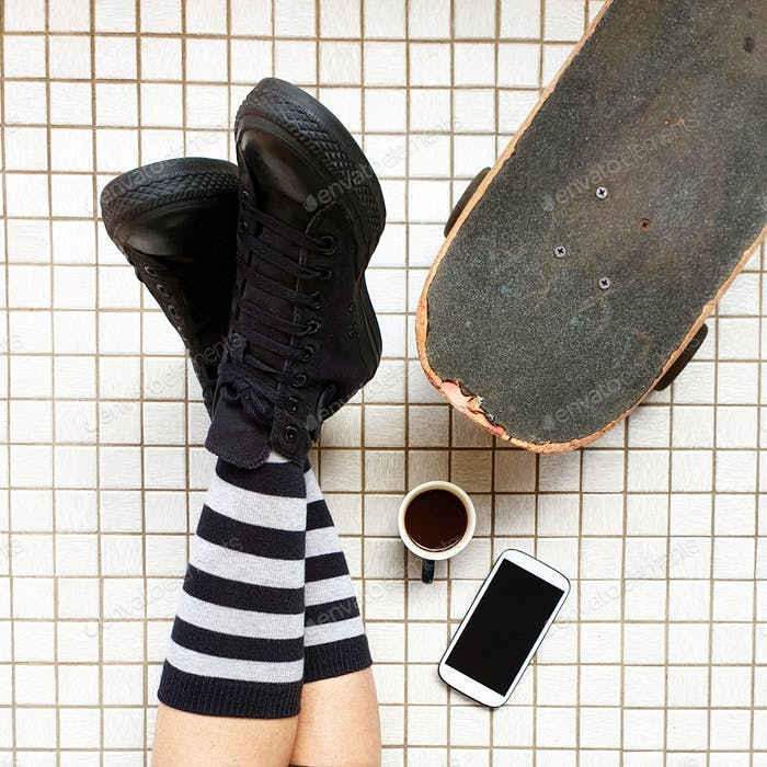 Skateboard lifestyle,Black canvas skate shoes,striped socks,legs crossed at ankle ,coffee,mobile pho