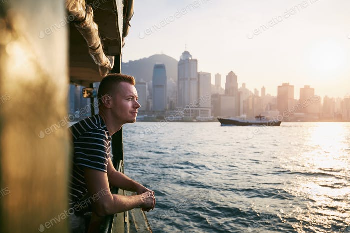 Young man (traveler) looking from boat against modern city at beautiful sunset. Cityscape with skysc