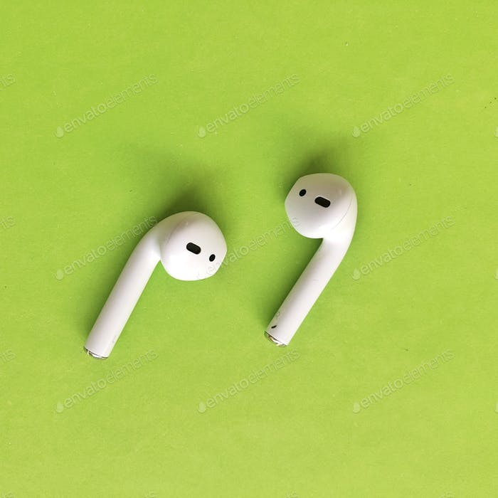 White apple AirPods earphones on green bold bright background